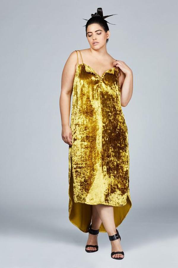 Woman wearing a gold velvet cocktail dress.