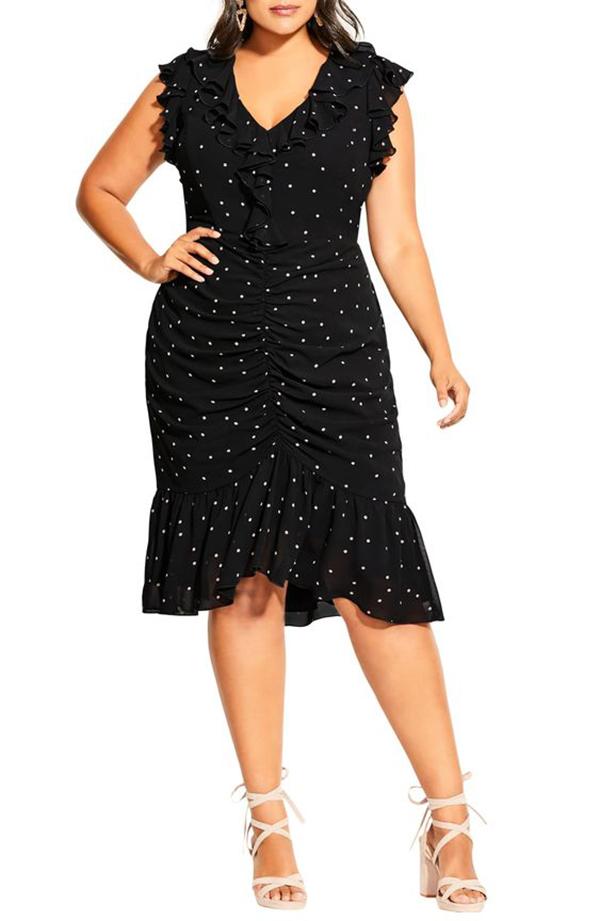 Woman wearing a black polka dot cocktail dress.