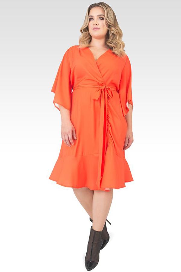 Woman wearing an orange cocktail dress.