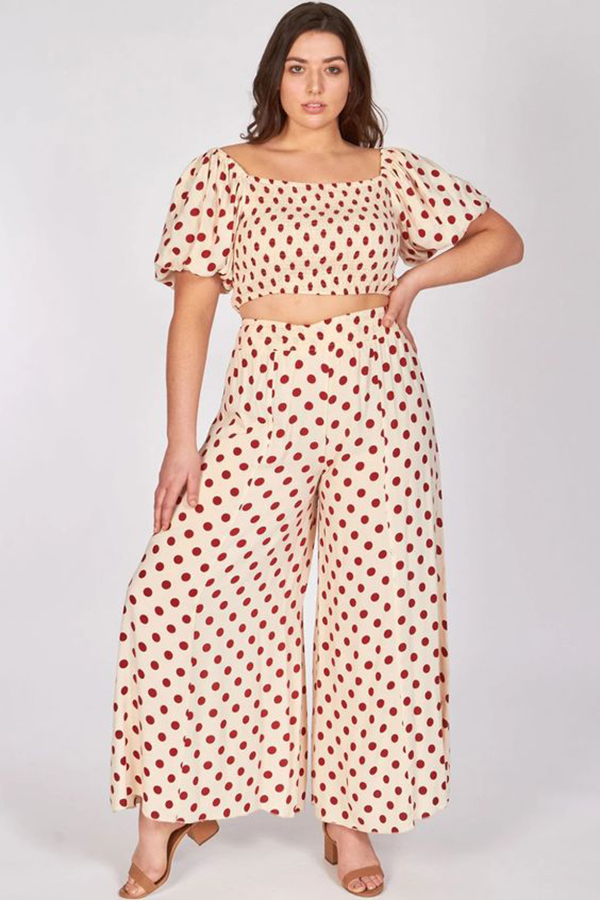 A plus-size model wearing a red and white polka dot matching set.