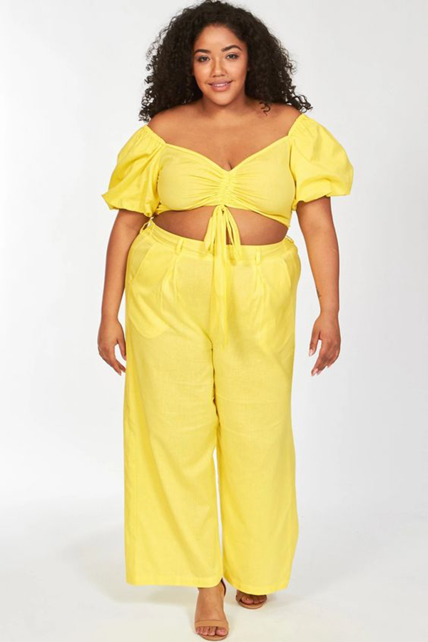 A plus-size model wearing a yellow matching set.
