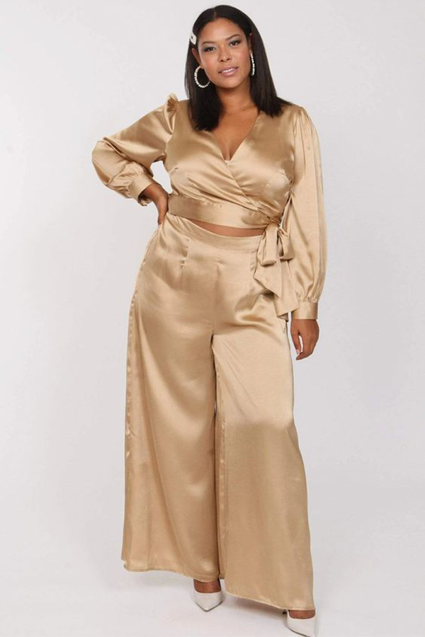 A plus-size model wearing a champagne matching set.