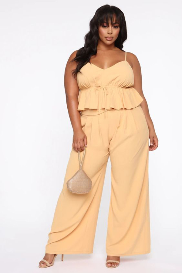 A plus-size model wearing a light orange matching set.
