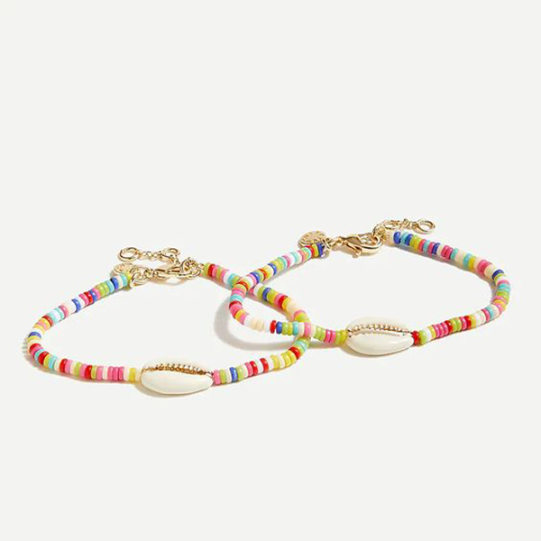 A pair of rainbow beaded bracelets with cowrie shells on them.