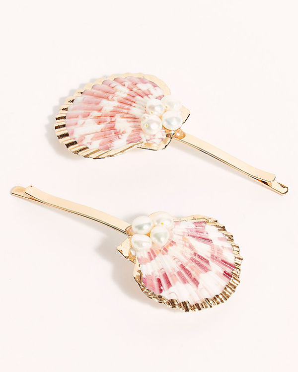 A pair of hair barrettes with scallop shells on them.