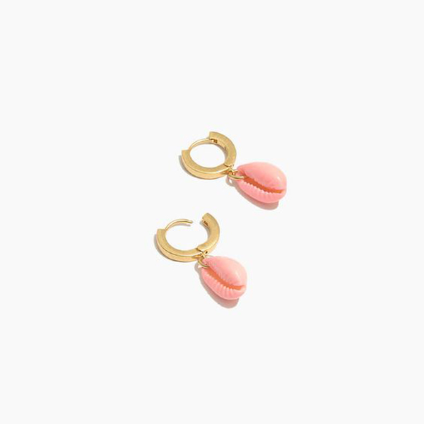 A pair of small gold hoop earrings with pink cowrie shells hanging from them.