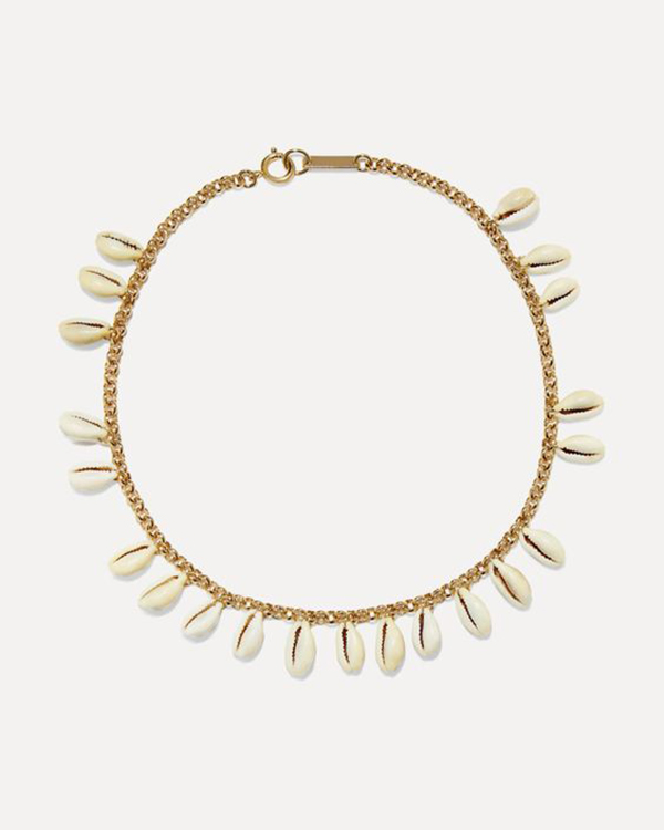 A gold chain choker with cowrie shells on it.