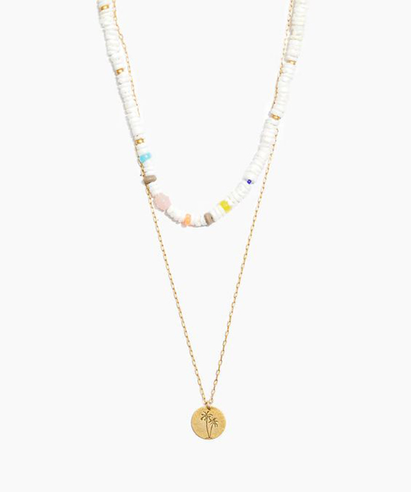 A pair of layered necklaces, one of which is lined with rounded puka shell beads.