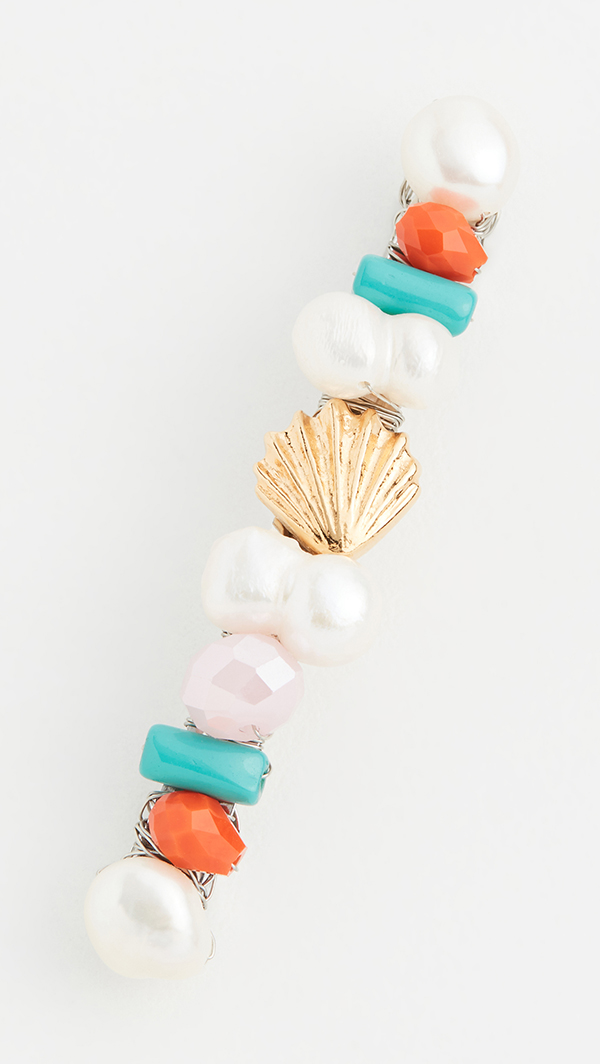 A hair barrette with beads, pearls, and metal shells on it.