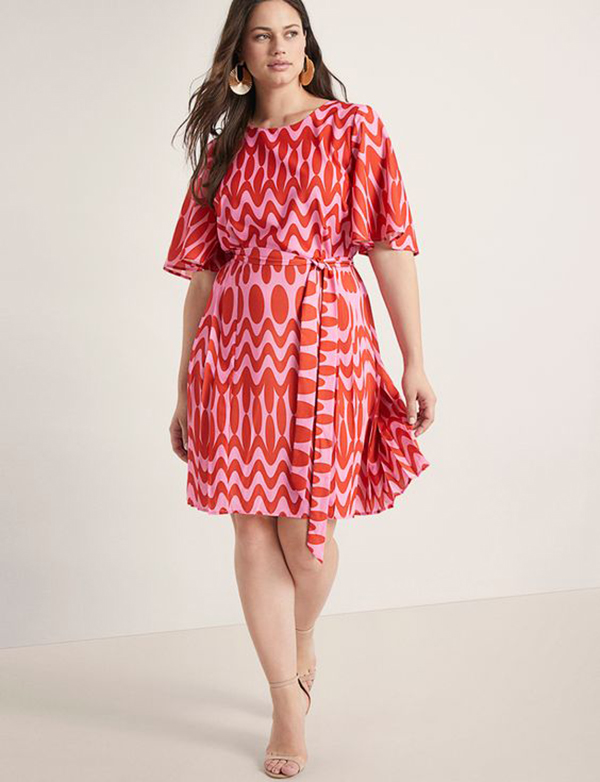 A plus-size model wearing a red and pink printed dress.