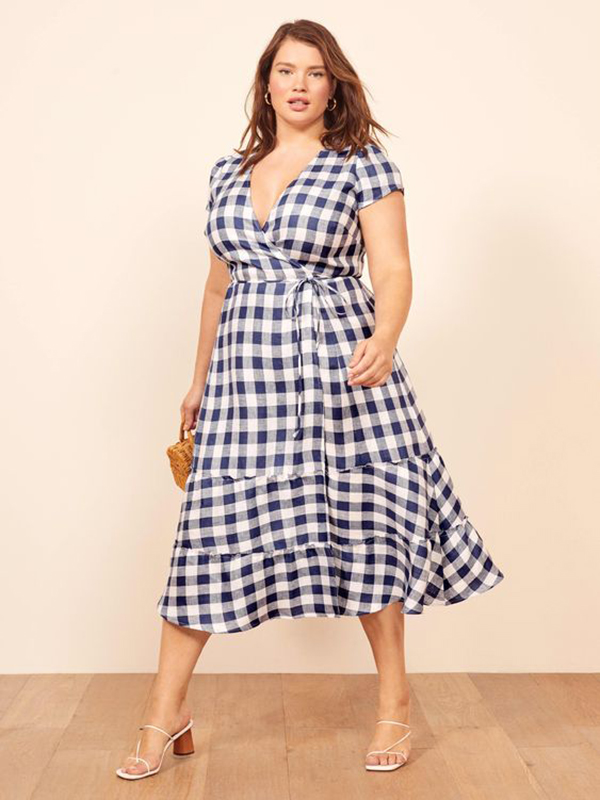 A plus-size model wearing a blue gingham dress.