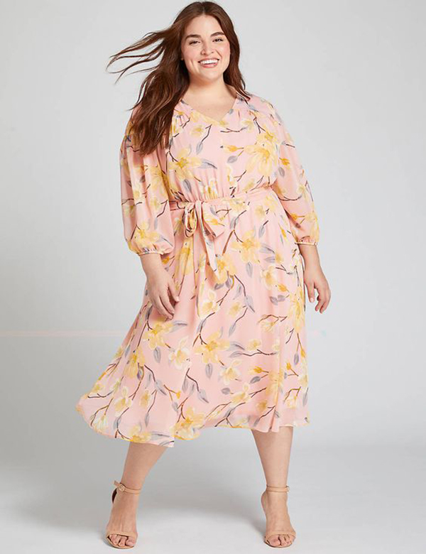 A plus-size model wearing a pink floral dress.