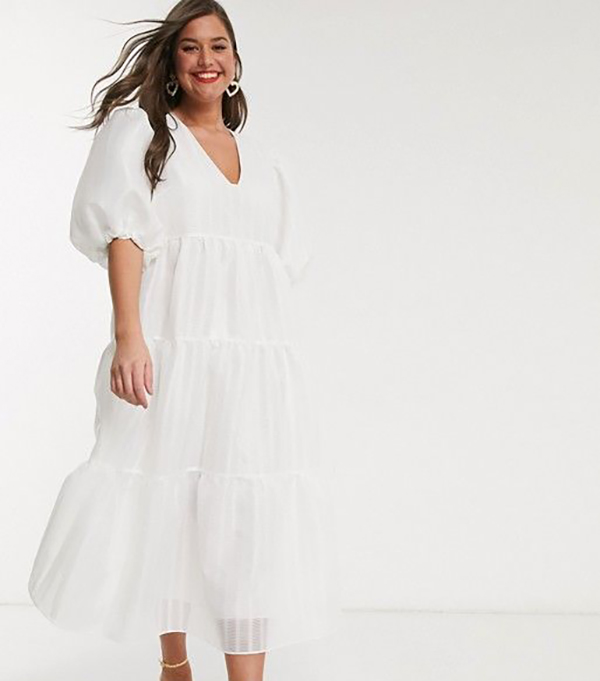 A plus-size model wearing a puff-sleeve white dress.