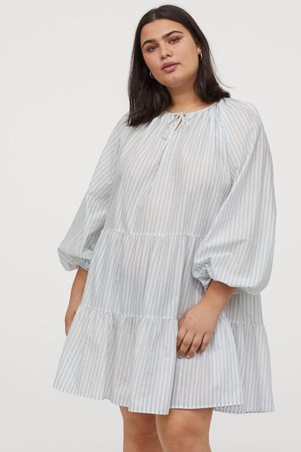 A plus-size model wearing a light blue dress.