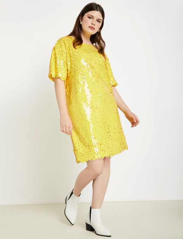 A plus-size model wearing a yellow sequin dress.