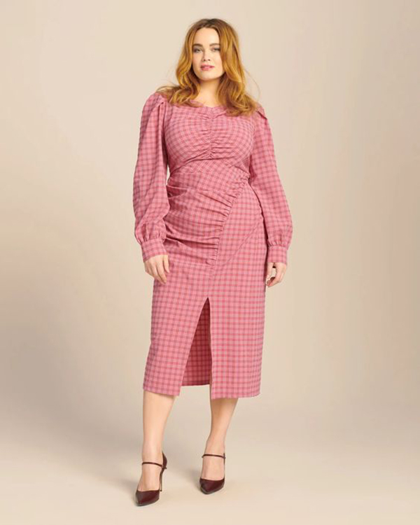 A plus-size model wearing a pink dress.