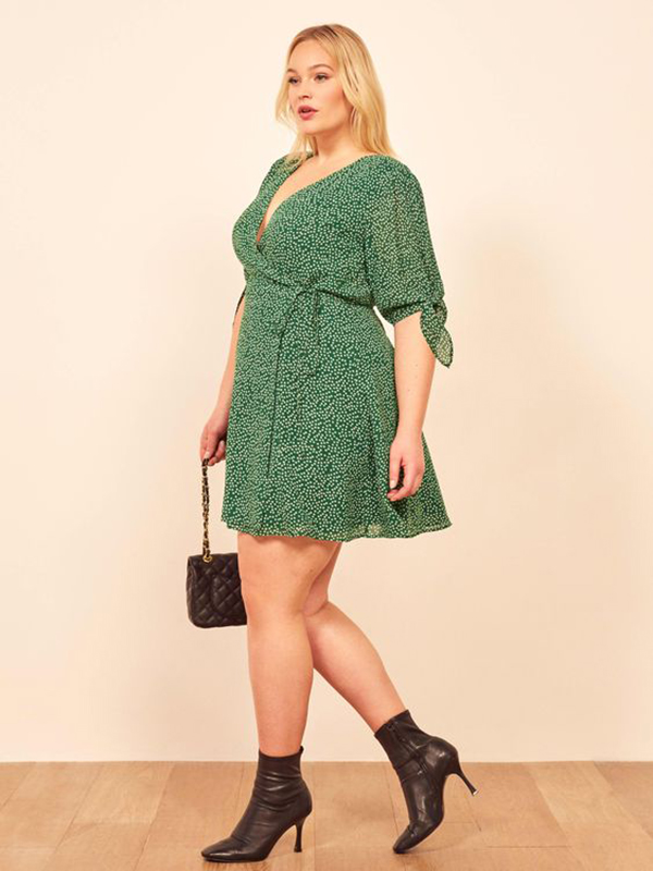 A plus-size model wearing a green printed dress.