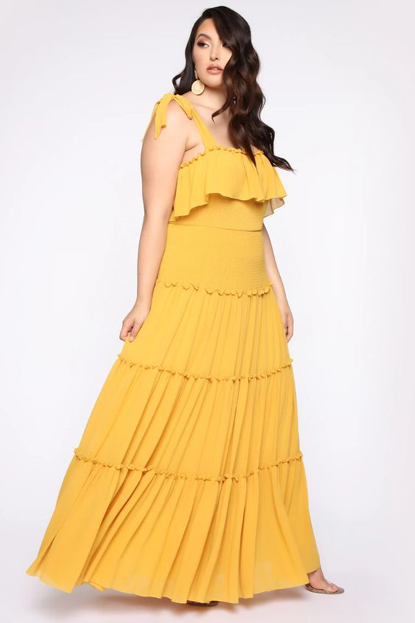 A plus-size model wearing a yellow maxi dress.