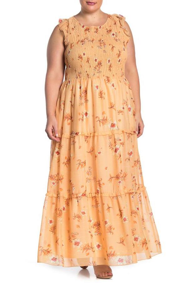 A plus-size model wearing a peach floral dress.