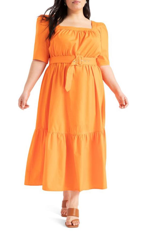 A plus-size model wearing an orange midi dress.