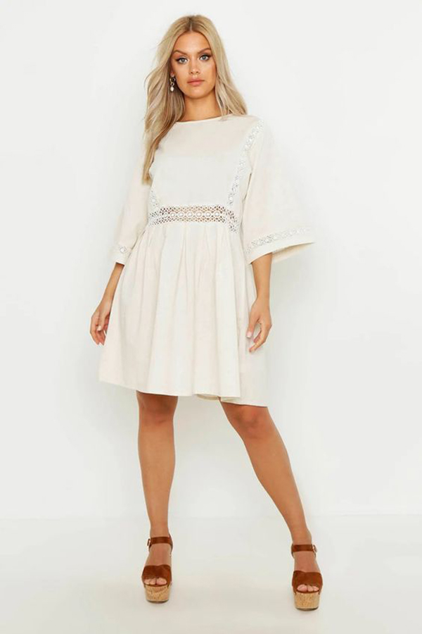 A plus-size model wearing a white sundress.