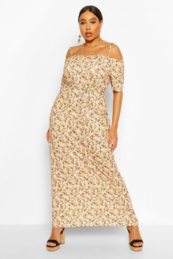 A plus-size model wearing an off-the-shoulder floral maxi dress.