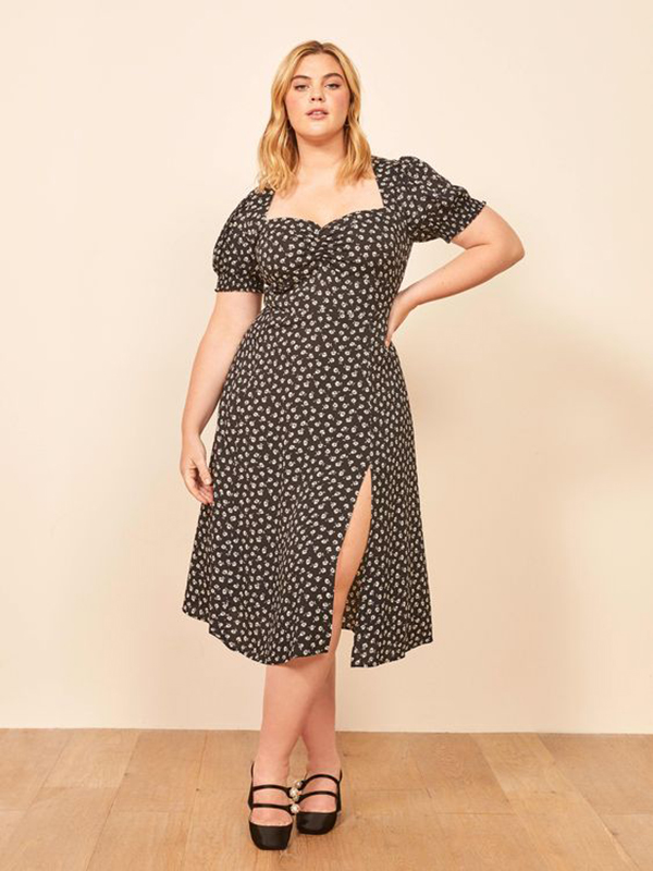 A plus-size model wearing a floral puff-sleeve dress.