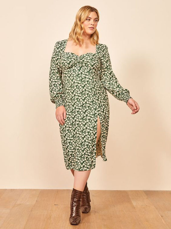 A plus-size model wearing a green floral midi dress.