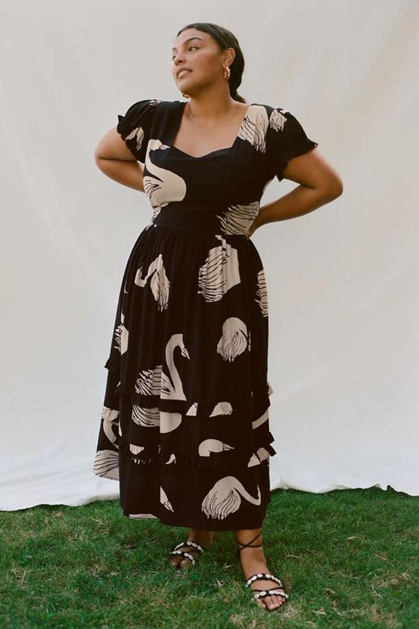 A plus-size model wearing a black printed midi dress.