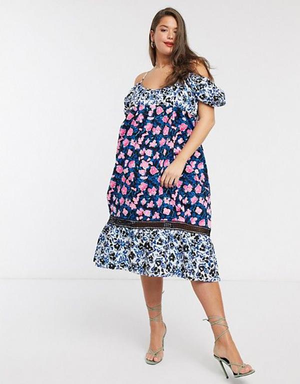 A plus-size model wearing a patchwork floral midi dress.