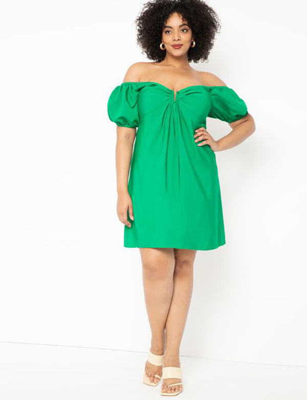 A plus-size model wearing an off-the-shoulder green dress.