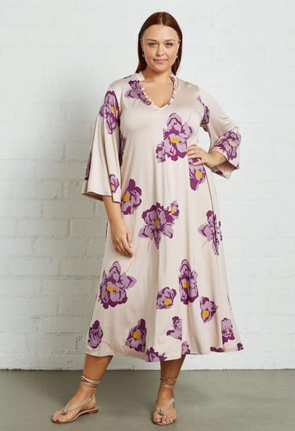 A plus-size model wearing a floral midi dress.