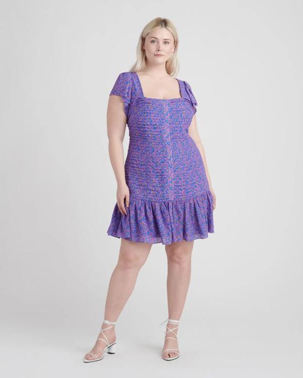 A plus-size model wearing a printed purple dress.