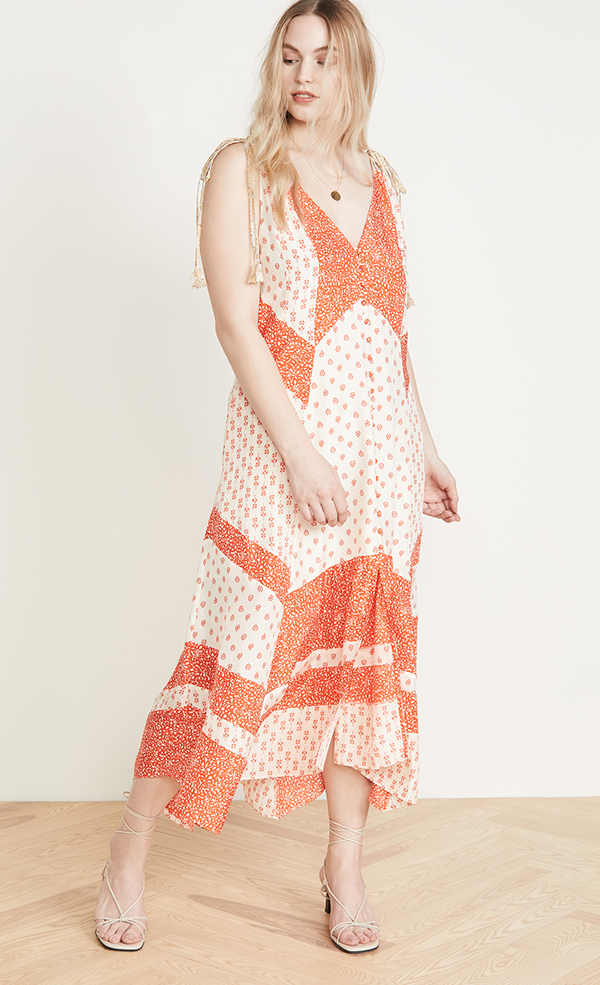 A plus-size model wearing an orange patchwork dress.