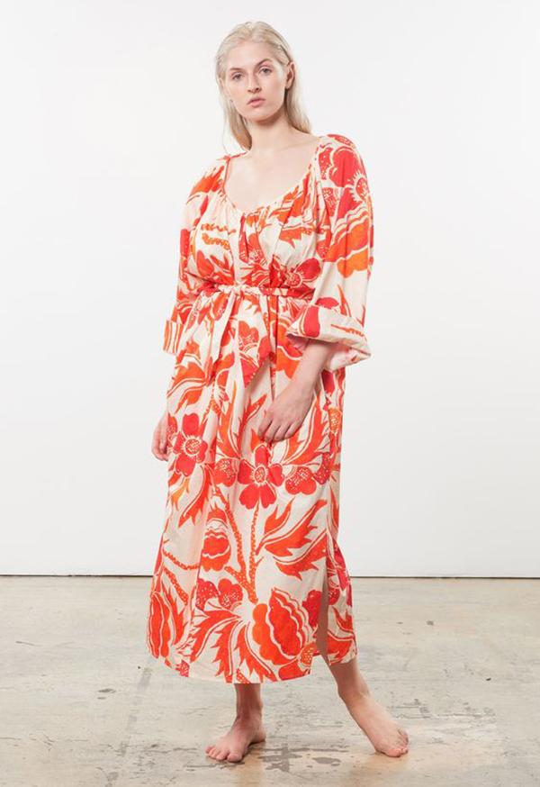 A plus-size model wearing an orange printed midi dress.