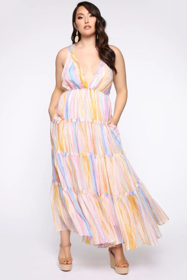 A plus-size model wearing a colorful maxi dress.