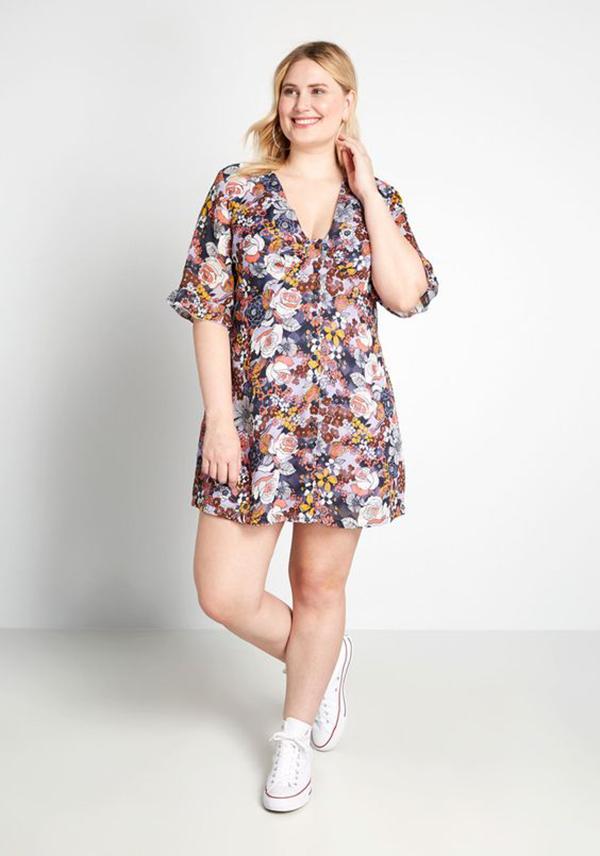 A plus-size model wearing a floral mini dress.