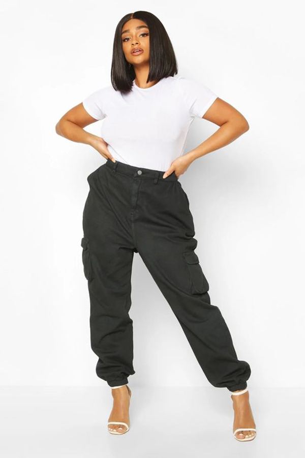 A plus-size model wearing black cargo pants.