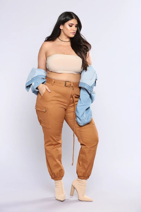 A plus-size model wearing light brown cargo pants.