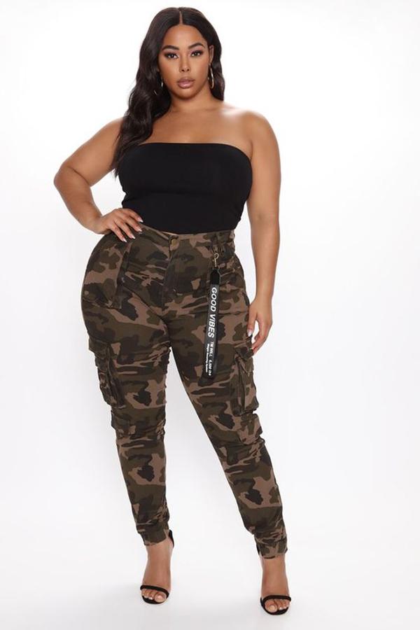 A plus-size model wearing camo cargo pants.
