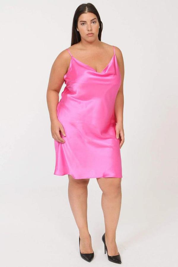 A plus-size model wearing a neon pink slip dress.
