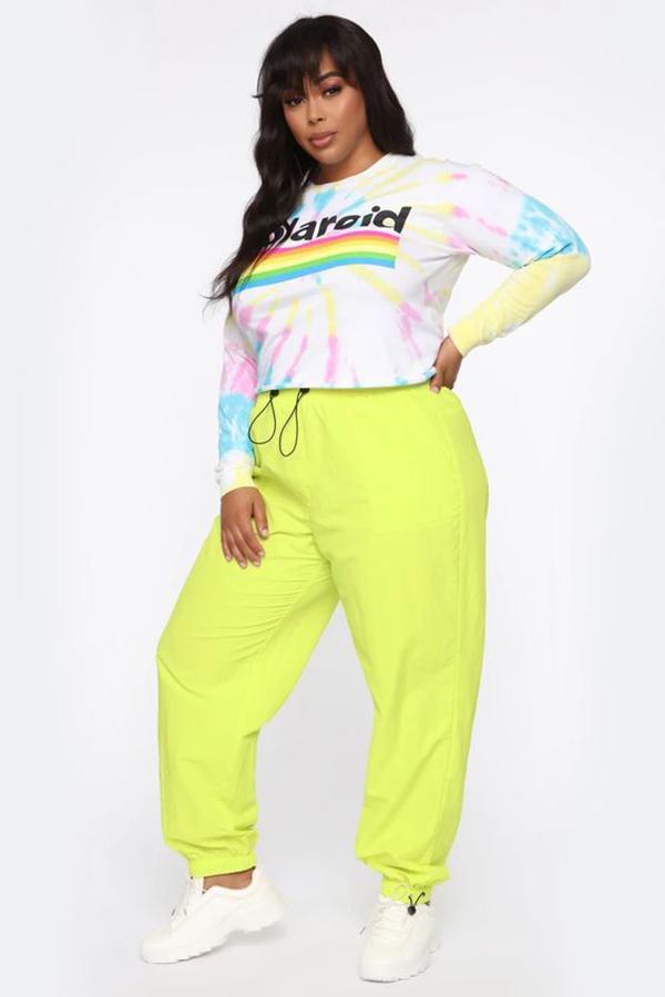 A plus-size model wearing neon yellow sweatpants.