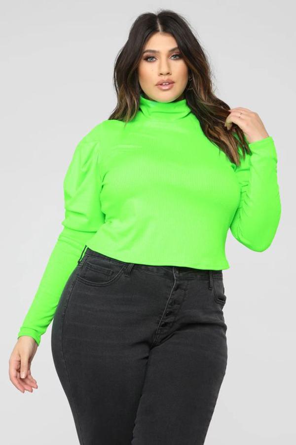 A plus-size model wearing a neon green sweater.