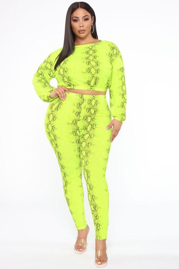A plus-size model wearing a neon yellow, snake print matching set.