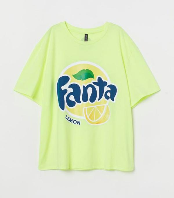 A plus-size model wearing a neon yellow-green Fanta T-shirt.