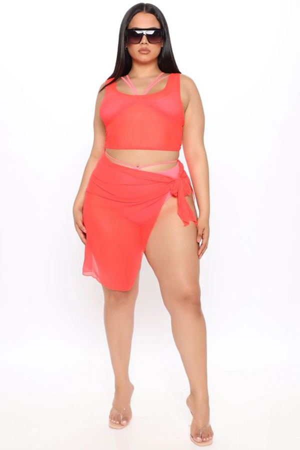 A plus-size model wearing a neon coral swim cover-up two-piece.