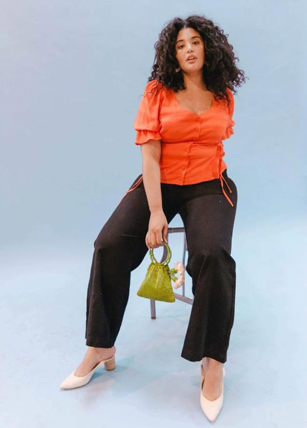 A plus-size model wearing a neon orange top.