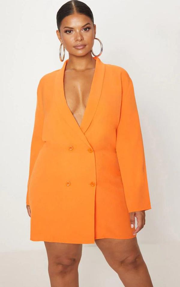 A plus-size model wearing a neon orange blazer.