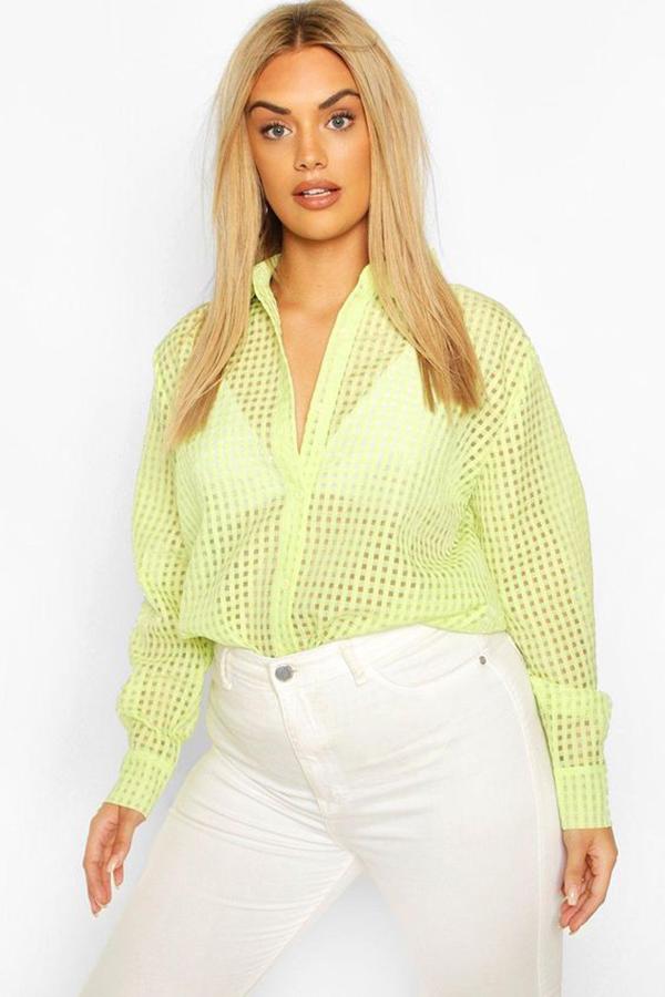 A plus-size model wearing a neon yellow-green blouse.