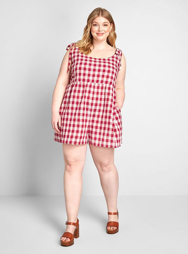 A plus-size model wearing a red gingham romper.